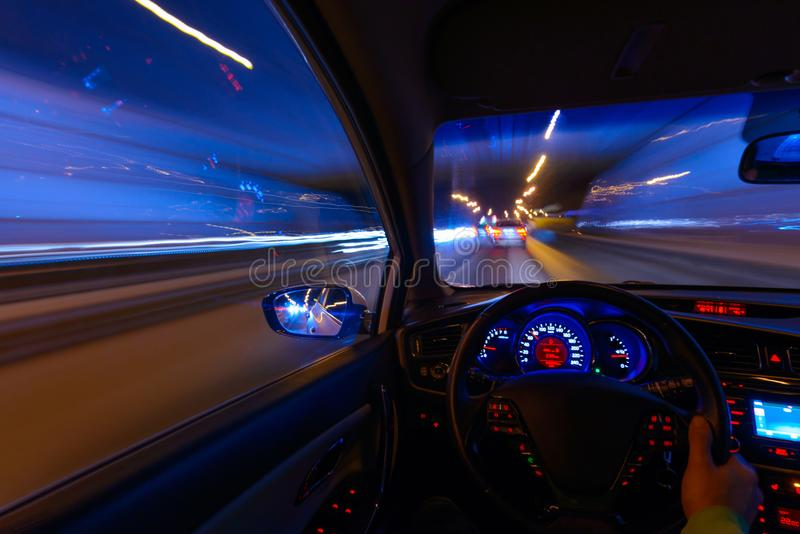Rörelse av bilen på natten på landshuvudvägen på en hög hastighet av visningen från insidan med chauffören Hand på royaltyfria bilder