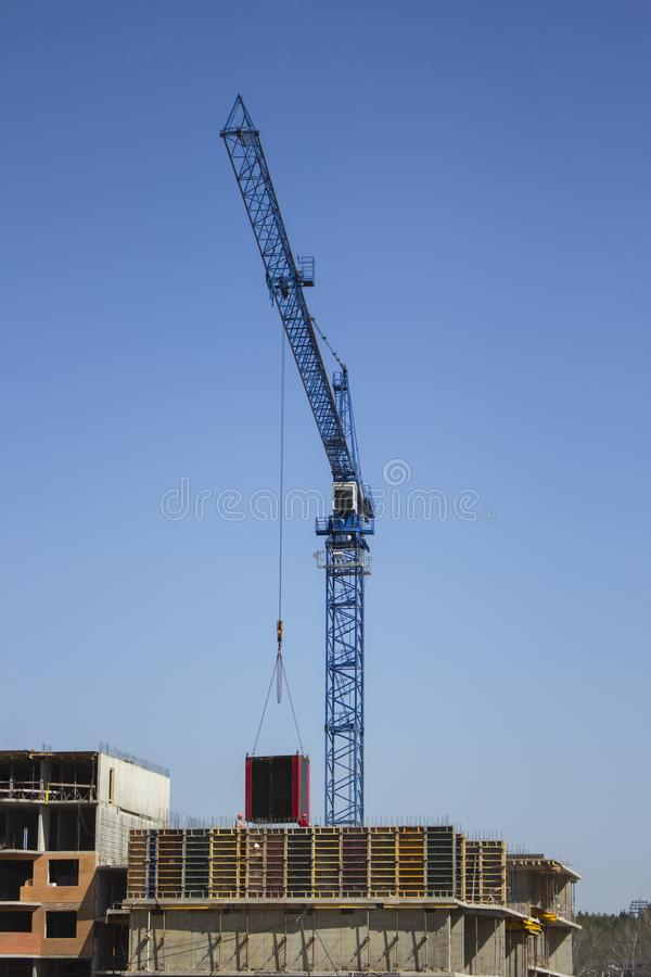 Rörelse av last vid en konstruktionskran Kranmaterialgolvet Betong för modern teknologi för konstruktion monolitisk arkivfoton