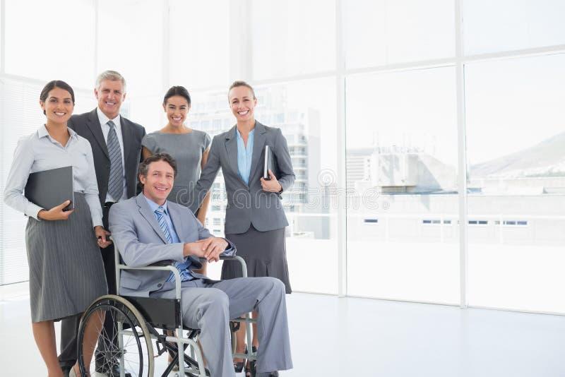 Rörelsehindrad affärsman med hans kollegor som ler på kameran arkivbild