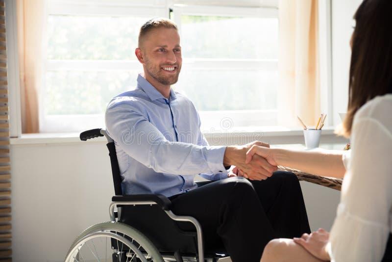 Rörelsehindrad affärsman Shaking Hand With hans partner arkivbild
