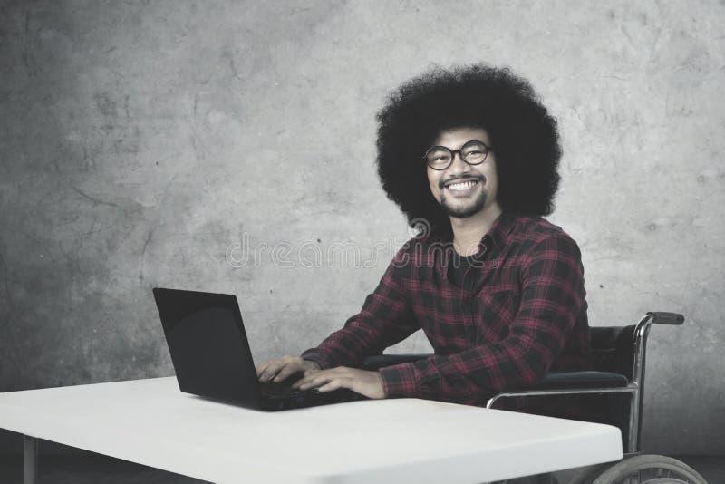 Rörelsehindrad affärsman som arbetar med bärbara datorn arkivbilder