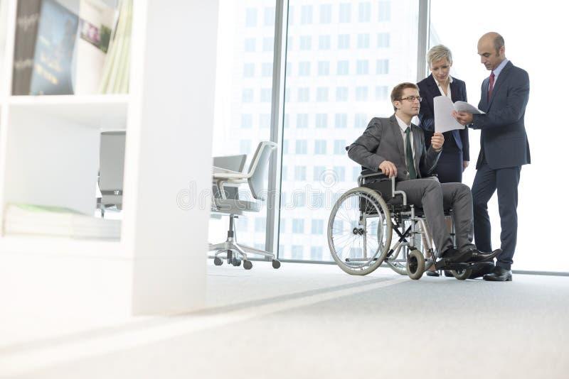 Rörelsehindrad affärsman som diskuterar över dokument med kollegor i styrelse på kontoret royaltyfri fotografi