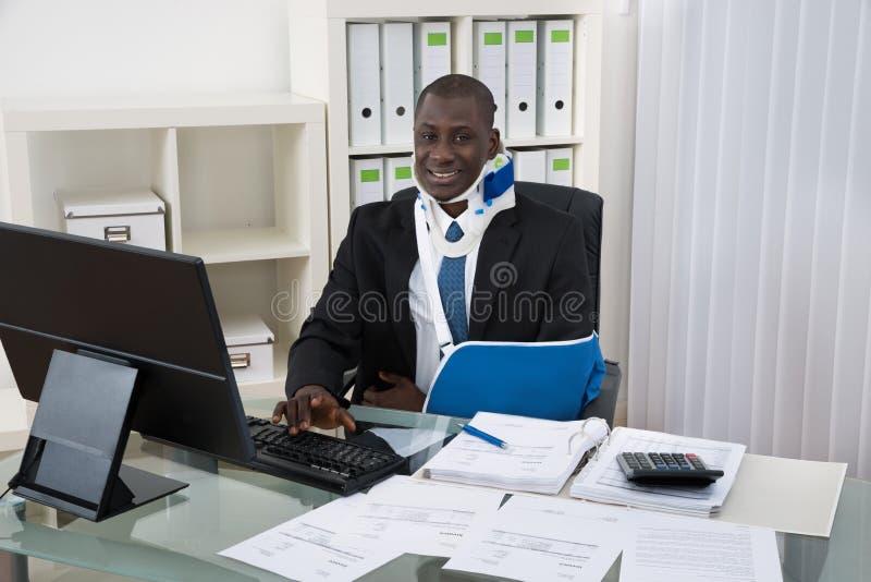 Rörelsehindrad affärsman Working In Office arkivfoton
