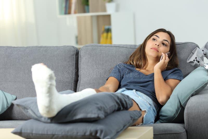 Rörelsehindrad allvarlig kvinna som talar på telefonen på en soffa royaltyfria bilder