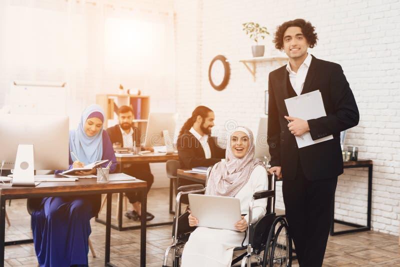 Rörelsehindrad arabisk kvinna i rullstolen som i regeringsställning arbetar Kvinnan poserar med den manliga coworkeren arkivbild