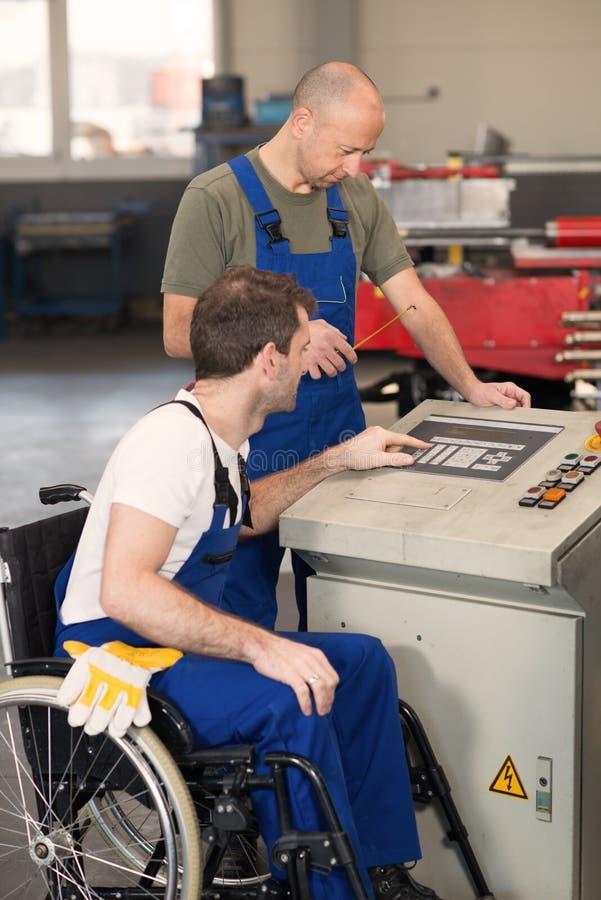 Rörelsehindrad arbetare i rullstol i fabrik och kollega arkivfoto