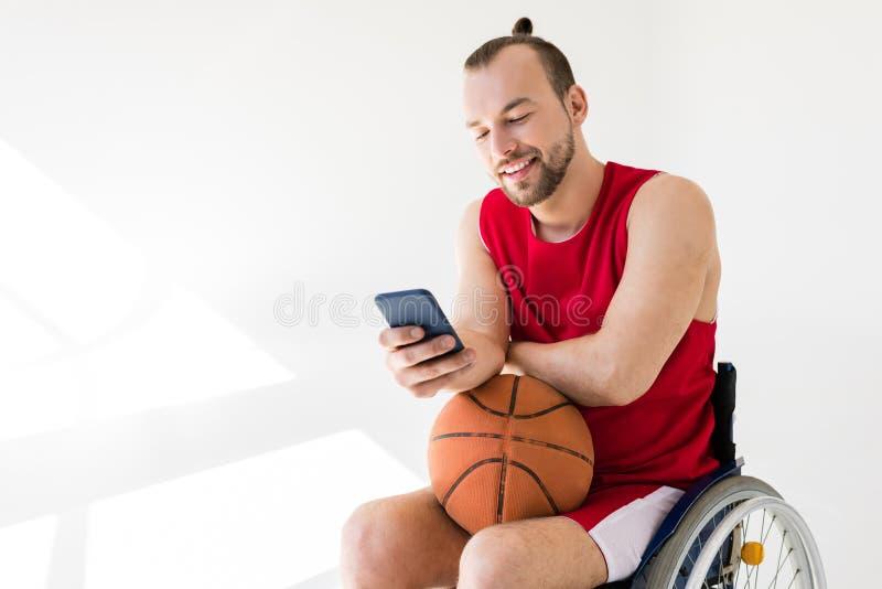 Rörelsehindrad basketspelare som använder smartphonen royaltyfri bild