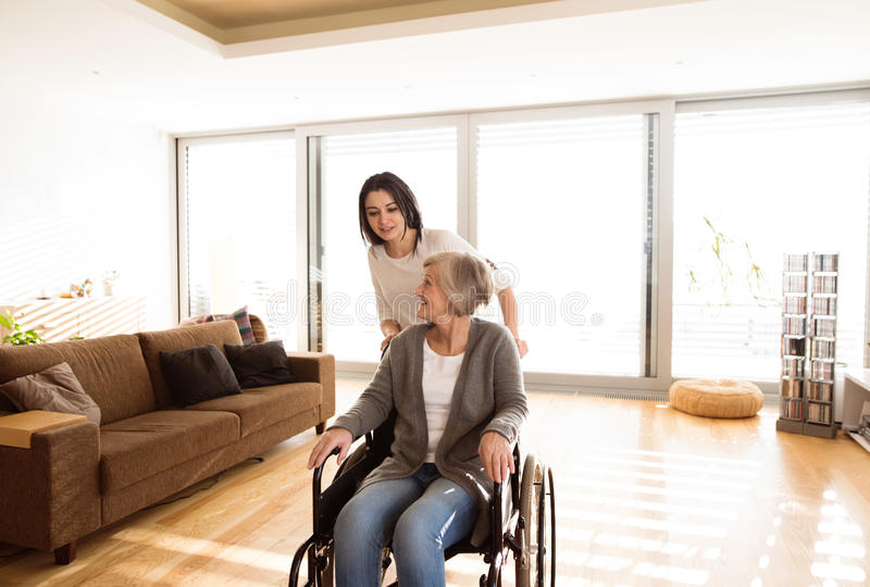 Rörelsehindrad hög kvinna i rullstol med hennes unga daugher royaltyfria foton
