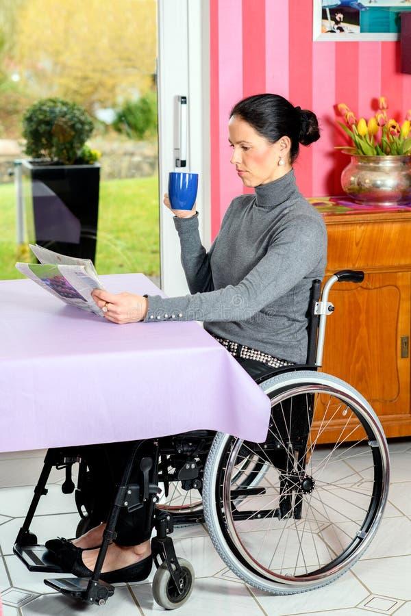 Rörelsehindrad kvinna i tidning och drink för rullstol hemmastadd läs- arkivfoton