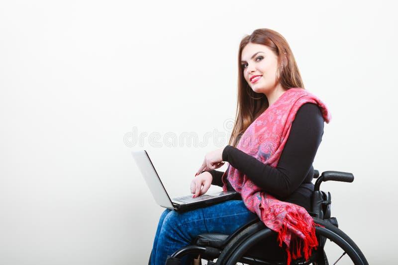 Rörelsehindrad kvinna med bärbara datorn på rullstolen royaltyfri bild