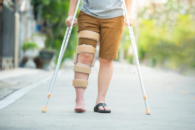 Rörelsehindrad kvinna med kryckor eller serviceanseende för gå pinne eller knäi den tillbaka sidan, halv kropp royaltyfri fotografi