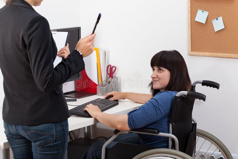 Rörelsehindrad kvinna på rullstolen som talar med chefen arkivfoton
