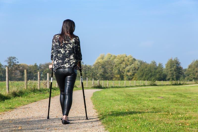 Rörelsehindrad kvinna som går på kryckor i natur fotografering för bildbyråer