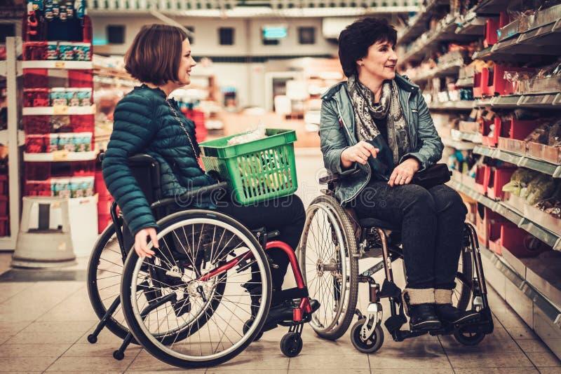Rörelsehindrad kvinna två i rullstolar i en livsmedelsbutik royaltyfria bilder