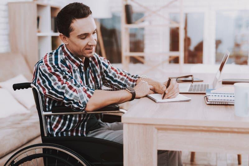 Rörelsehindrad man för barn på rullstolen som hemma arbetar royaltyfri bild
