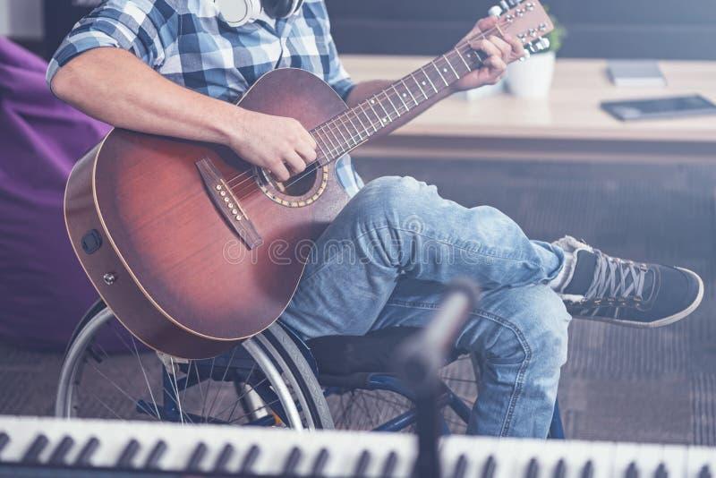 Rörelsehindrad man för barn som tycker om spela gitarren i studion royaltyfria bilder