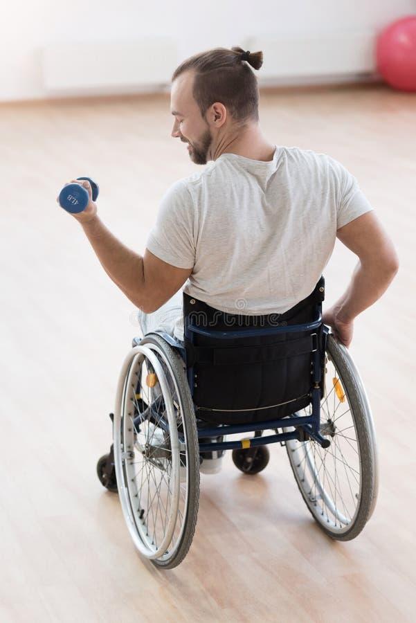 Rörelsehindrad man för förtjust barn som övar med vikter i idrottshallen arkivfoton