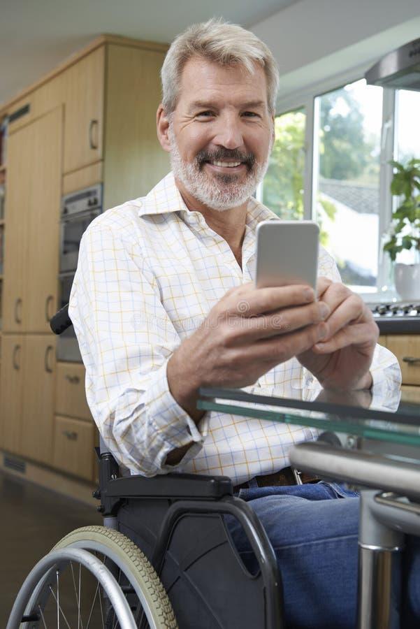 Rörelsehindrad man i rullstolen som hemma smsar på mobiltelefonen royaltyfria bilder