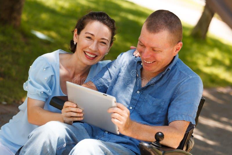 Rörelsehindrad man med hans fru som har gyckel, medan genom att använda minnestavlan på arkivfoton