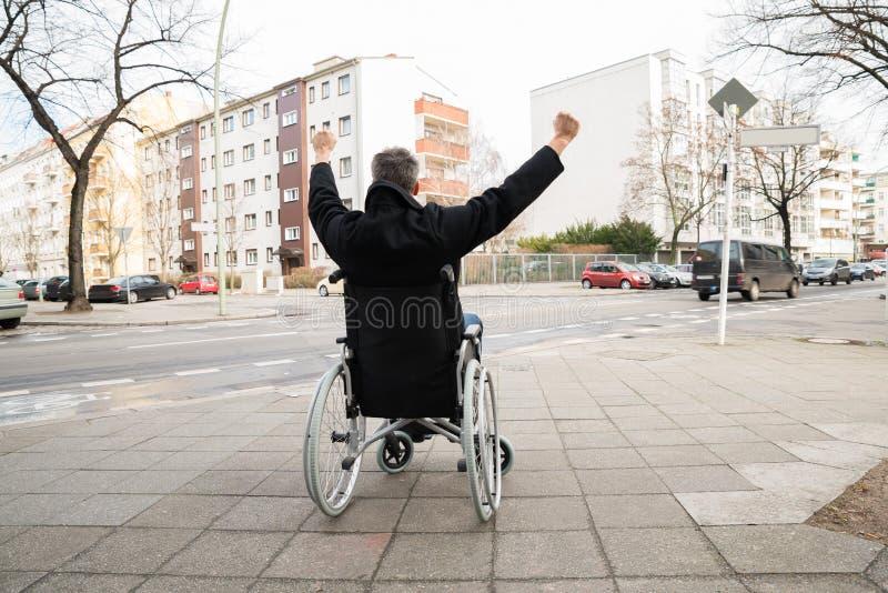 Rörelsehindrad man på rullstolen med den lyftta handen royaltyfria foton
