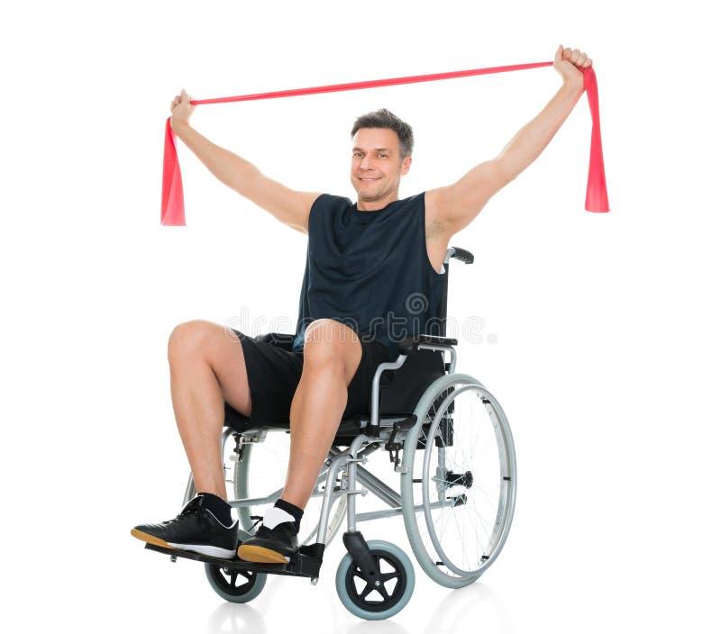 Rörelsehindrad man på rullstolen som övar med motståndsmusikbandet arkivfoton