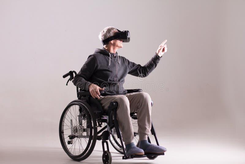 Rörelsehindrad man som bär VR-exponeringsglas arkivbild