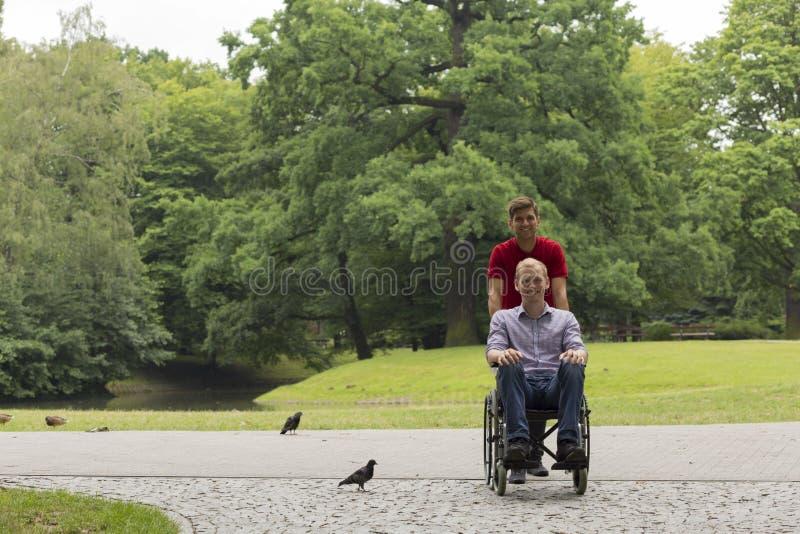 Rörelsehindrad man under en promenad i parkera med vännen arkivfoto