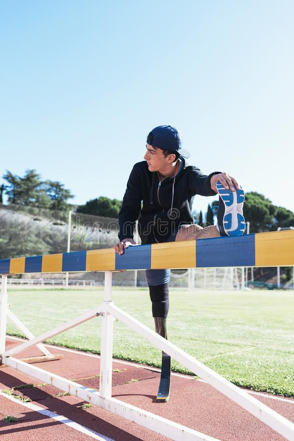 Rörelsehindrad manidrottsman nen som sträcker med benprotes Paralympic sportbegrepp arkivfoto