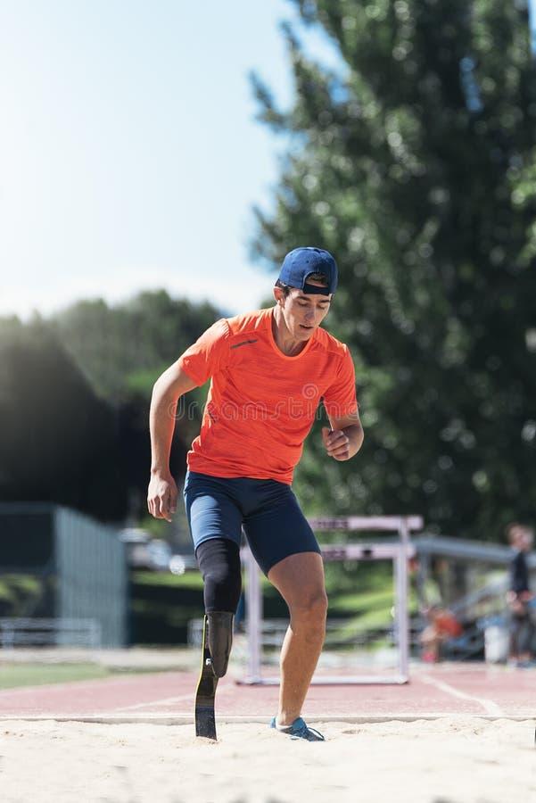 Rörelsehindrad manidrottsman nenbanhoppning med benprotes Paralympic Spo royaltyfri fotografi