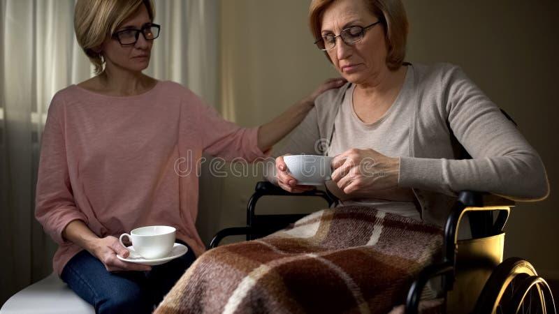Rörelsehindrad moder och dotter som dricker te och att tala om liv som att bry sig barn royaltyfri bild