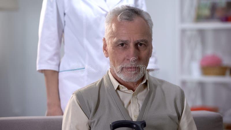 Rörelsehindrad pensionär som bakom, service- och omsorgsitter på lagledaren, sjuksköterska begrepp arkivbild