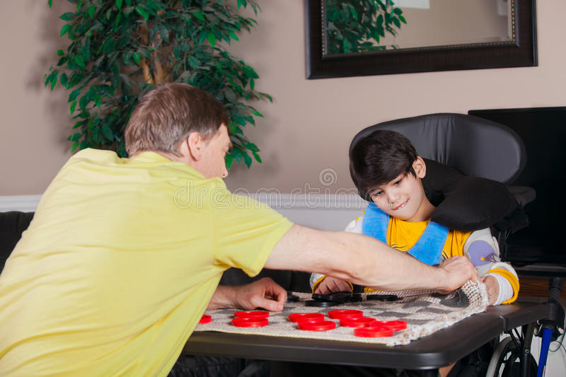 Rörelsehindrad pojke i rullstolen som spelar kontrollörer med den hemmastadda fadern arkivfoton