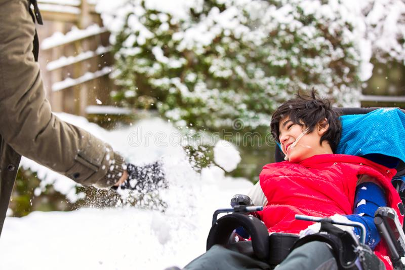 Rörelsehindrad pojke i rullstolen som spelar i vintersnö arkivfoton