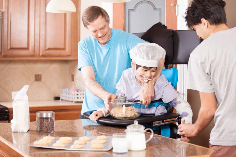 Rörelsehindrad pojke i stekheta kakor för stander med fadern och brodern royaltyfri foto
