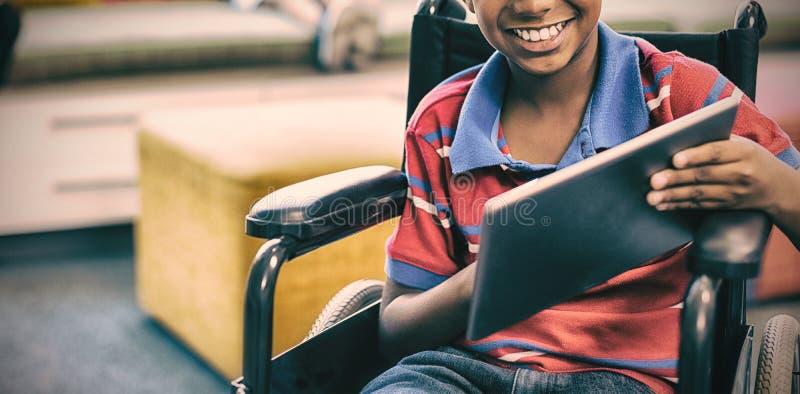 Rörelsehindrad skolpojke på rullstolen genom att använda den digitala minnestavlan i arkiv arkivfoto