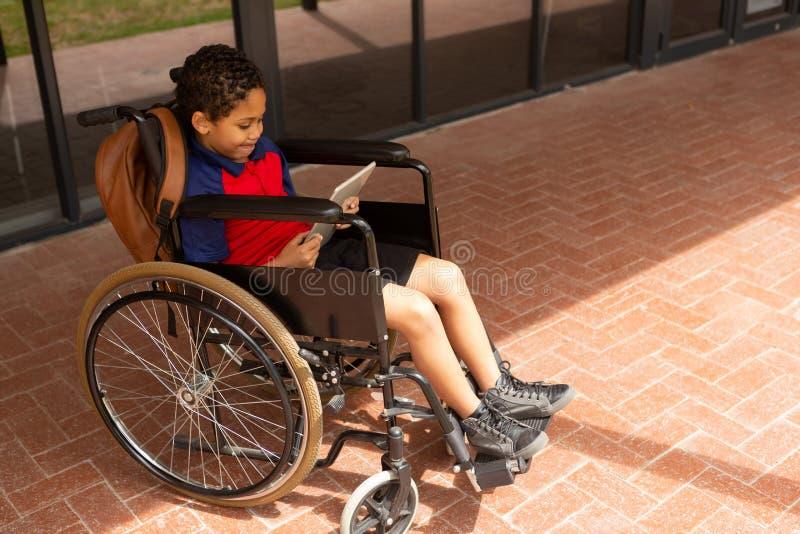 Rörelsehindrad skolpojke som använder den digitala minnestavlan i korridor arkivfoton