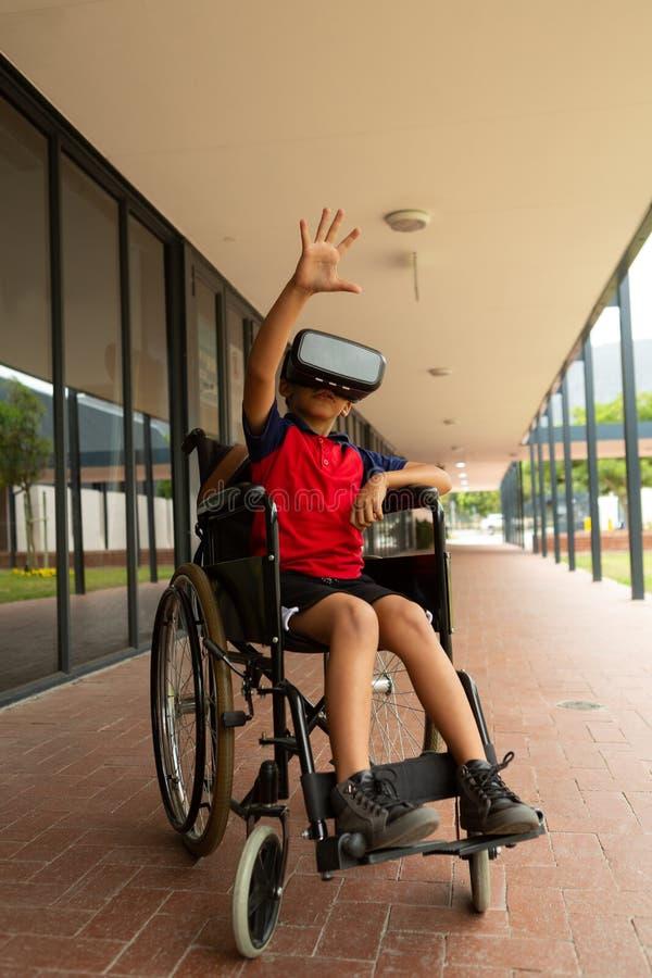 Rörelsehindrad skolpojke som använder virtuell verklighethörlurar med mikrofon i korridor royaltyfri bild