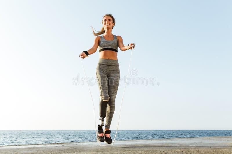 Rörelsehindrad sportkvinnabanhoppning med överhopprepet arkivfoton