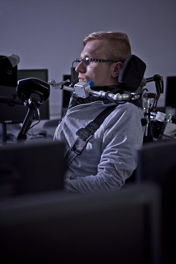 Rörelsehindrad student som arbetar med hans dator arkivfoton