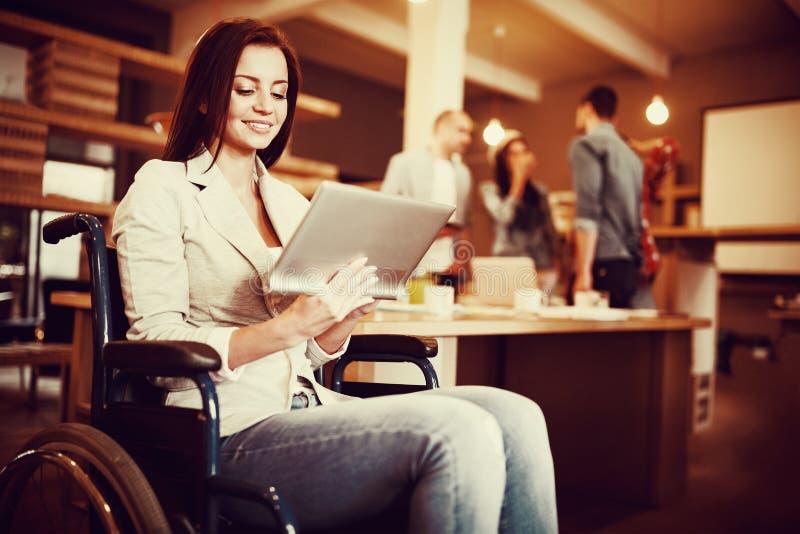 Rörelsehindrad ung affärskvinna som använder den digitala minnestavlan arkivfoto