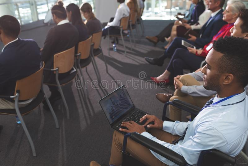 Rörelsehindrad ung affärsman som använder bärbara datorn under seminarium royaltyfri bild