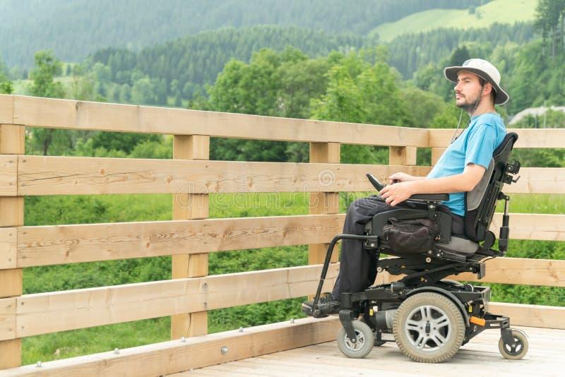 Rörelsehindrad ung man i elektrisk rullstol på en strandpromenad som tycker om hans frihet och observerar naturen arkivfoton