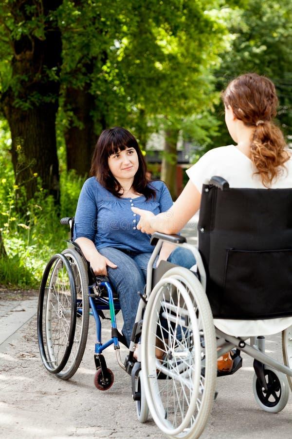 Rörelsehindrade flickor på rullstolar under samtal fotografering för bildbyråer