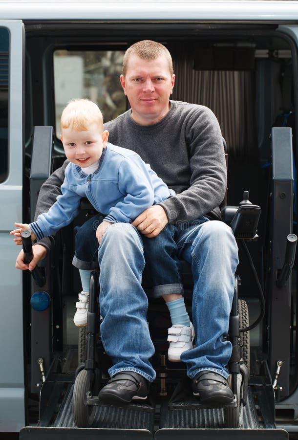 Rörelsehindrade män med sonen på rullstolelevator royaltyfria foton