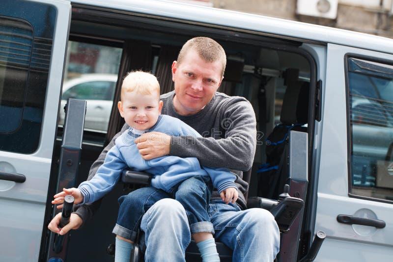 Rörelsehindrade män med sonen på rullstolelevator arkivbild