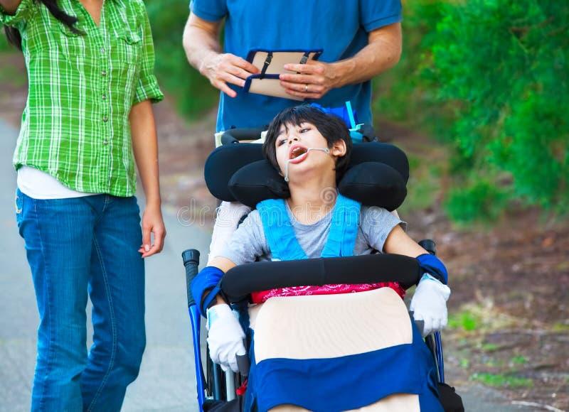 Rörelsehindrat barn i rullstol utomhus med anhörigvårdare eller familjen royaltyfria foton