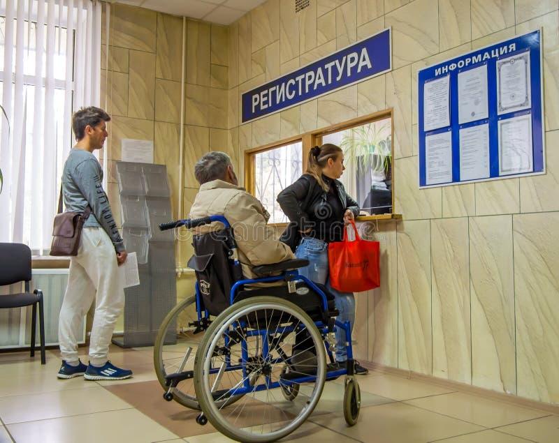 Rörelsehindrat vänta i linje på medicinsk institutions registrering arkivfoto
