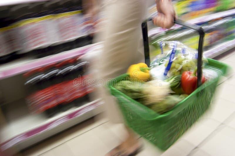 Rörelsesuddighet av den hållande shoppingkorgen för kvinna som går i Supermar arkivbilder