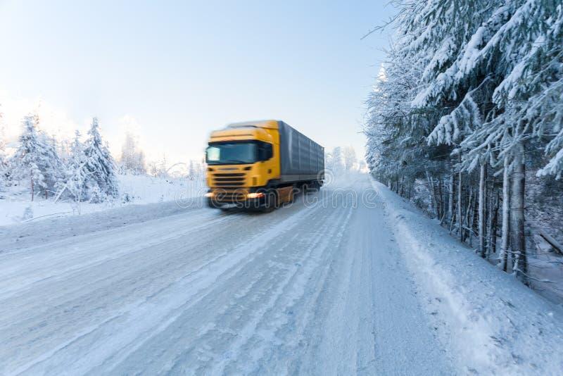 Rörelsesuddighet av en lastbil på vintervägen på frostig solig dag royaltyfri foto