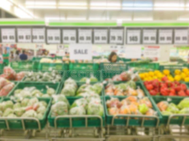 Rörelsesuddighet av frukthyllor som är till salu i supermarket med någon folkshopping royaltyfri fotografi